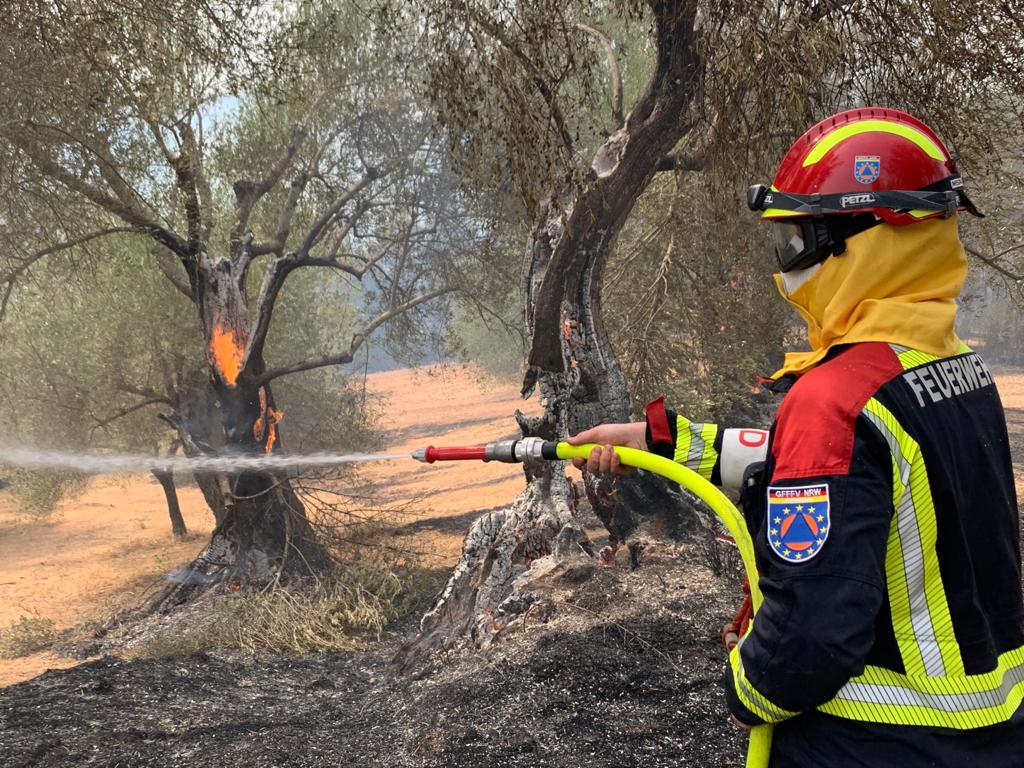 Ein Feuerwehrmann aus Deutschland löscht brennende Olivenbäume
